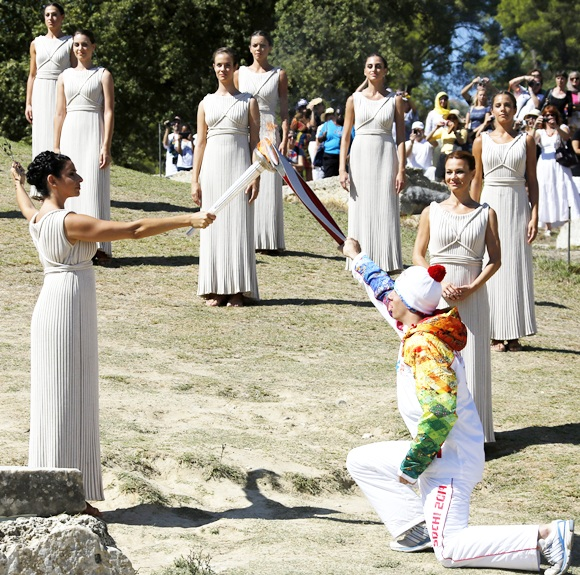 Greek actress Ino Menegaki, playing the role of High Priestess, passes the Olympic flame to Greek skier Yannis Antoniou, the first torchbearer of the torch relay, during a dress rehearsal for the torch lighting ceremony of the Sochi 2014 Winter Olympic Games
