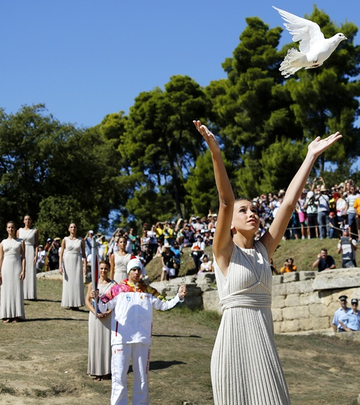 A Greek girl, wearing an ancient robe, releases a white dove during a dress rehearsal for the torch lighting ceremony of the Sochi 2014 Winter Olympic Games