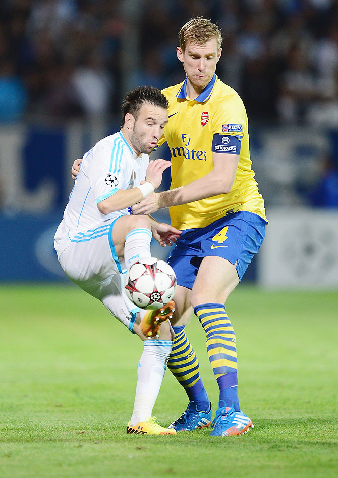 Per Mertesacker of Arsenal battles with Mathieu Valbuena of Olympique Marseille during their UEFA Champions League group F match on September 18