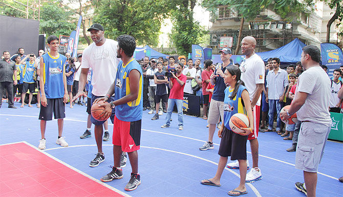 Horace Grant teaches a kid how to score a basket during NBA Jam Mumbai edition on Sunday