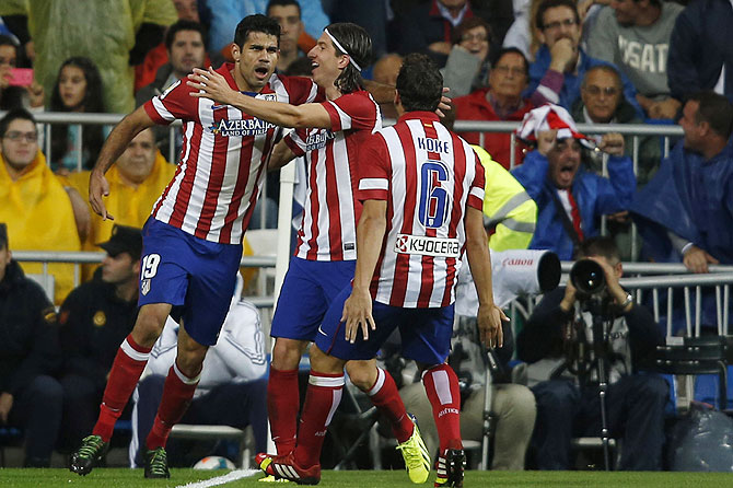 Atletico Madrid's Diego Costa (left) celebrates a goal with teammates Filipe and Koke (right) during the Spanish La Liga match against Real Madrid at Santiago Bernabeu stadium in Madrid on Saturday