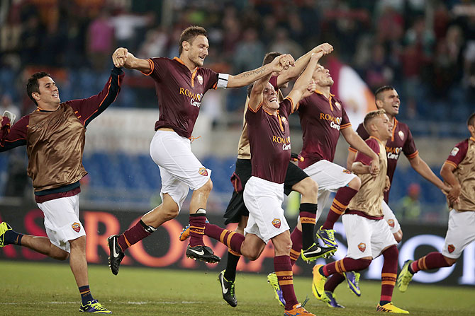 Roma players celebrate at the end of their Italian Serie A soccer match against Bologna at the Olympic stadium in Rome on Sunday