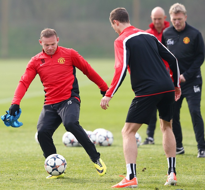 Wayne Rooney of Manchester United controls the ball past Jonny Evans during a training session