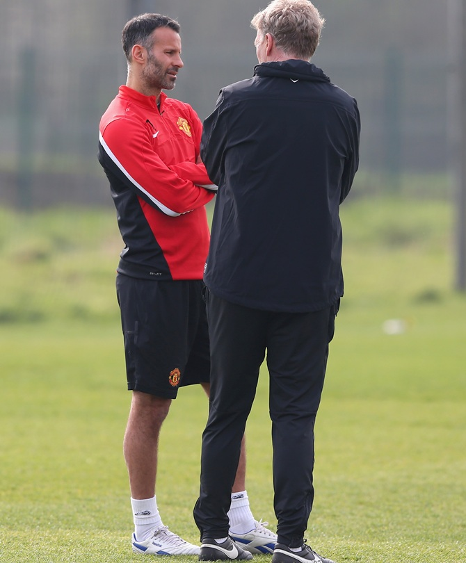 David Moyes the manager of Manchester United talks with Ryan Giggs