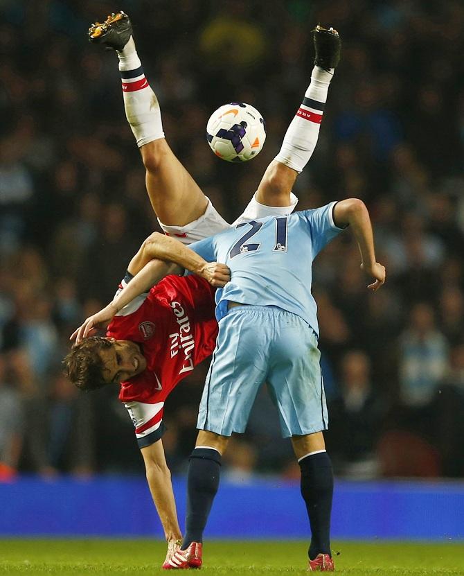 Arsenal's Mathieu Flamini, left, challenges Manchester City's David Silva