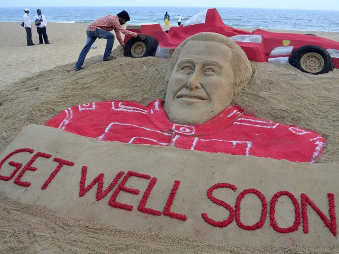Indian sand artist Sudarshan Pattnaik works on a sand sculpture   of Michael Schumacher to wish him a speedy recovery at Puri
