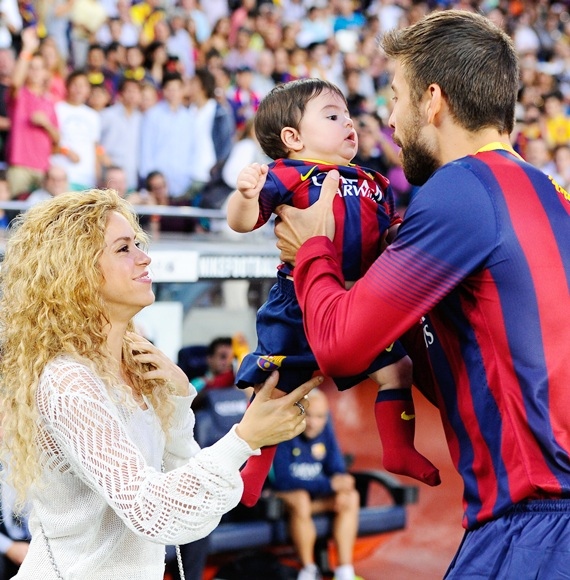 Shakira and Gerard Pique of FC Barcelona with their son Milan at a football match