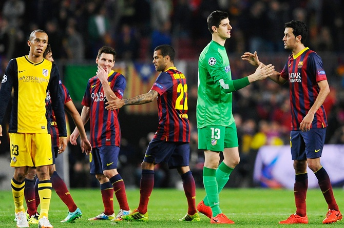 Goalkeeper Thibaut Courtois of Club Atletico de Madrid shakes hands   with Sergio Busquets of Barcelona as Lionel Messi of Barcelona grimaces