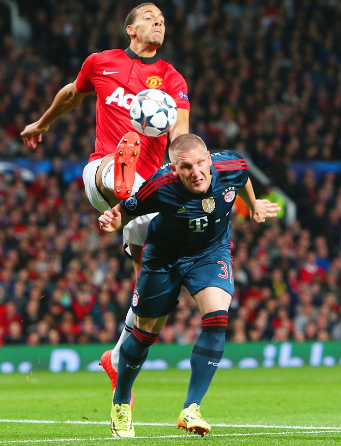 Rio Ferdinand of Manchester United and Bastian Schweinsteiger of Bayern Muenchen battle for the ball