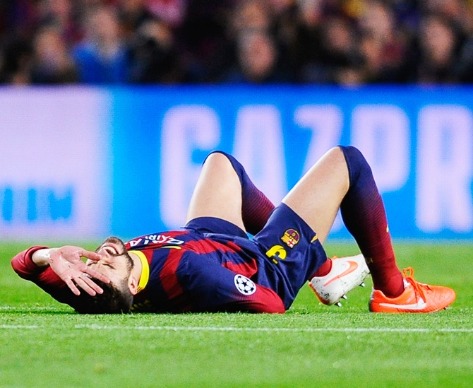 Gerard Pique of Barcelona grimaces before being substituted for an injury