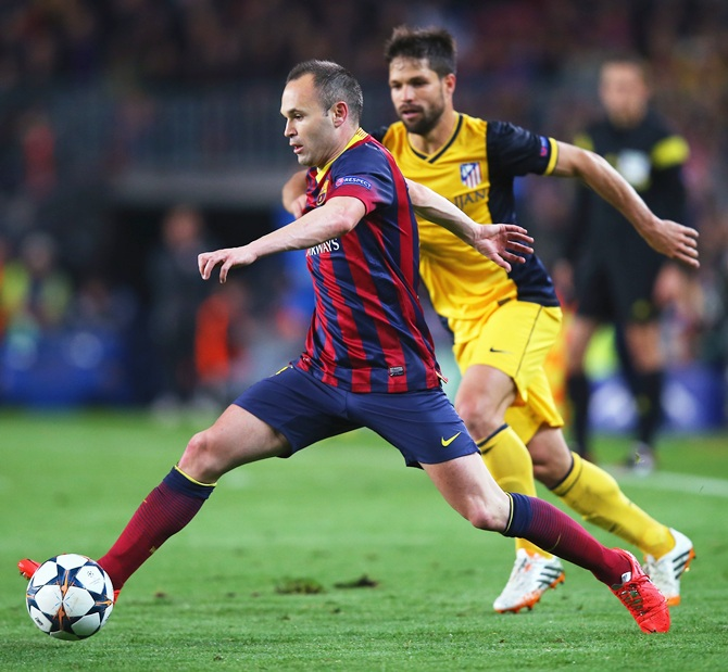 Andres Iniesta of Barcelona goes past Diego of Club Atletico de Madrid