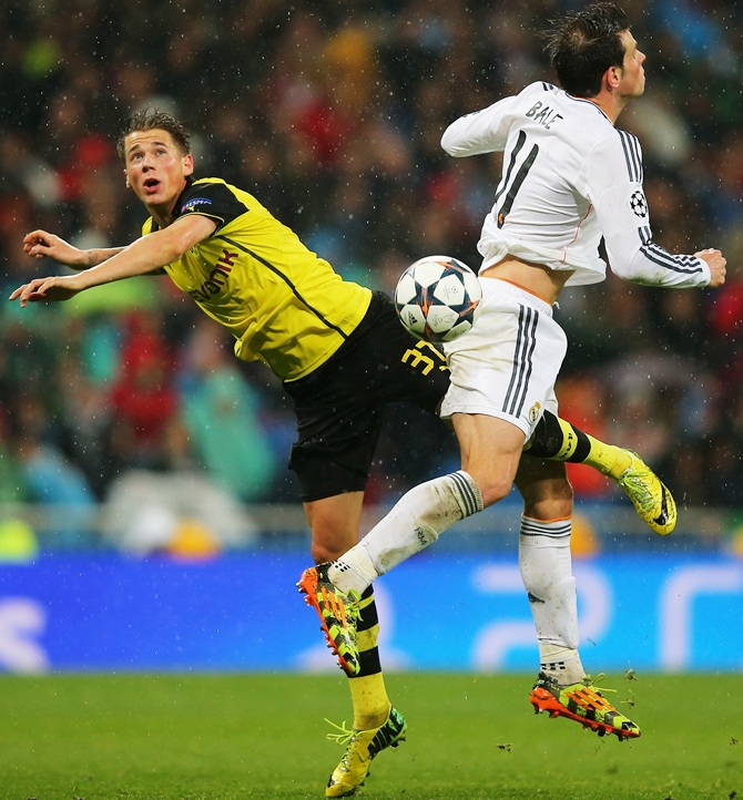 Erik Durm of Borussia Dortmund jumps with Gareth Bale of Real Madrid