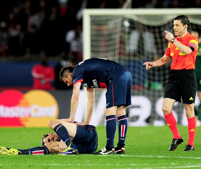 Thiago Motta of PSG checks on teammate Zlatan Ibrahimovic after he goes down injured