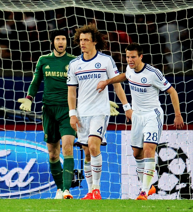 Goalkeeper Petr Cech,left, looks on in disbelief after David Luiz,centre, of Chelsea scores an own goal