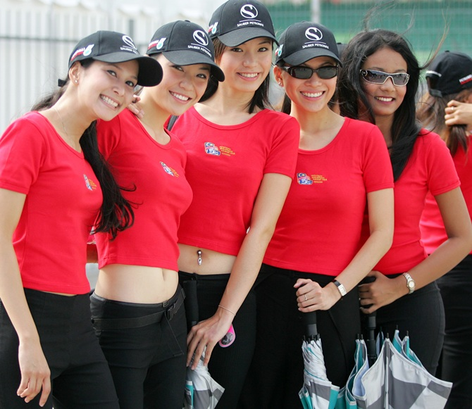 Grid girls pose for a photo after arriving on Sepang circuit for rehearsal on the eve of the Malaysian Grand Prix in Sepang, outside Kuala Lumpur, March 19, 2005