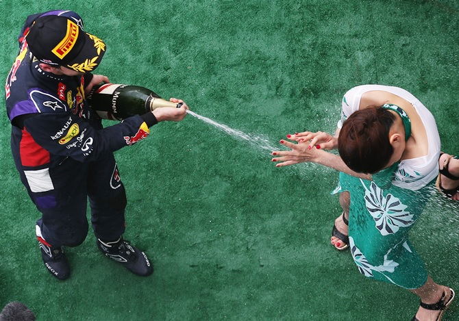 Third placed Sebastian Vettel of Germany and Infiniti Red Bull Racing sprays a presentation girl with champagne