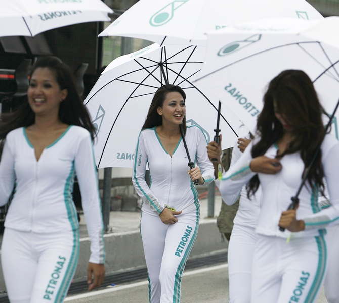 Petronas-sponsored grid girls walk through the pit lane before the third practice session at the Sepang International Circuit April 4, 2009