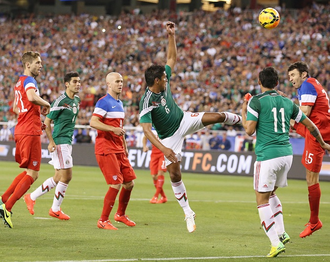Juan Carlos Valenzuela of Mexico attempts a shot defended by Michael Parkhurst of USA