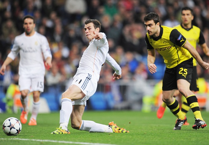 Gareth Bale of Real Madrid scores the opening goal watched by Sokratis Papastathopoulos of Borussia Dortmund