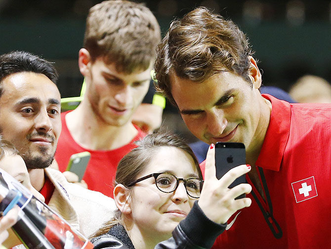 Switzerland's Roger Federer poses with a fan for a selfie after winning his Davis Cup quarter-final tennis match against Andrey Golubev of Kazakhstan on Sunday
