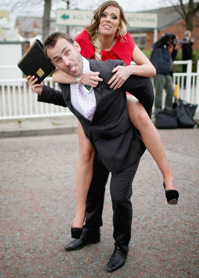 A man carries a girl as racegoers make their way home from Ladies Day