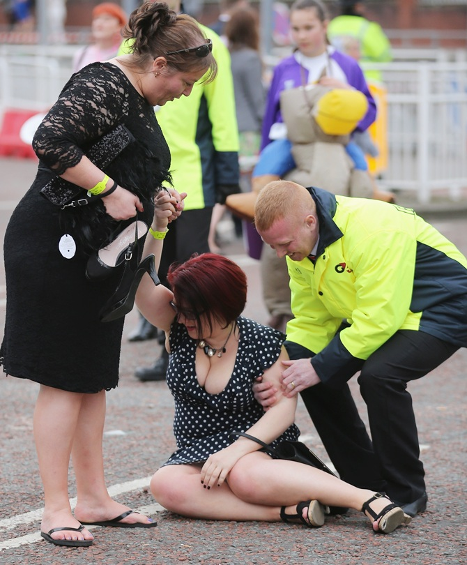 A woman is helped to her feet after tripping