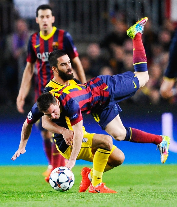 Lionel Messi of Barcelona is challenged by Arda Turan of Club Atletico de Madrid