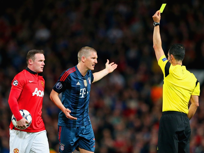 Wayne Rooney of Manchester United looks on as Bastian Schweinsteiger of   Bayern Muenchen receives a yellow card from Referee Carlos Velasco Carballo