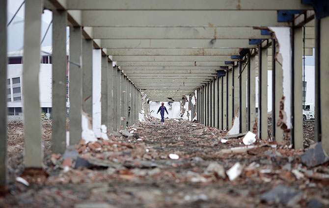 A worker walks at the work site of the Parque Olimpico Rio 2016 (Rio 2016 Olympic Park), which is being constructed over the former Jacarepagua race track