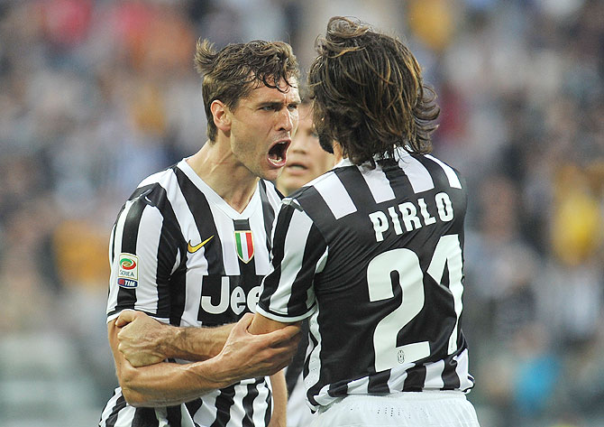 Fernando Lorente (Left) of Juventus celebrates with teammate Andrea Pirlo after scoring his second goal against Livorno at Juventus Arena in Turin on Monday