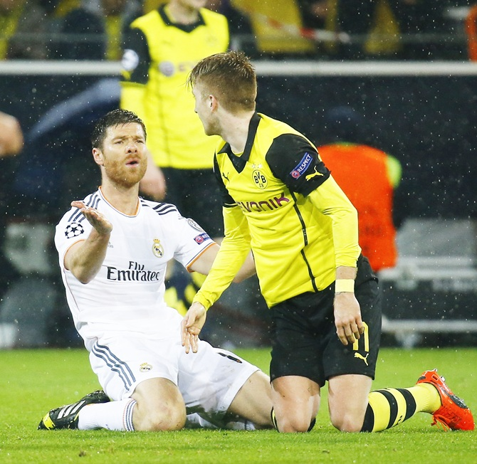 Real Madrid's Xabi Alonso,left, reacts in front of Borussia Dortmund's Marco Reus