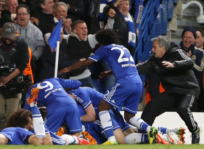 Chelsea's Demba Ba (hidden) celebrates with coach Jose Mourinho, right, and teammates after scoring the second goal