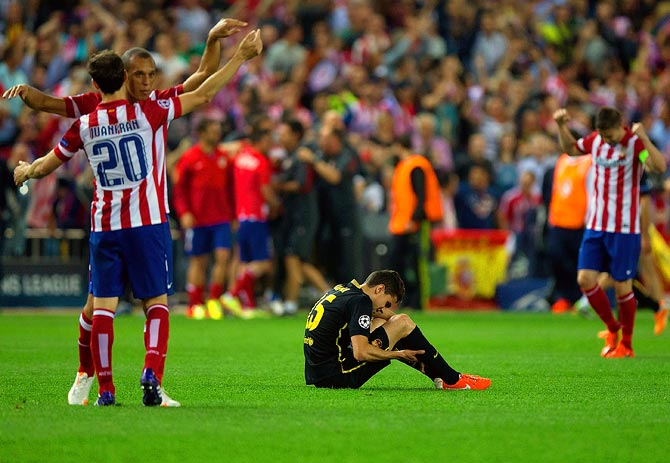 Atletico Madrid players celebrate as Barcelona's Marc Batra sits dejected after the end of the match in Madrid.