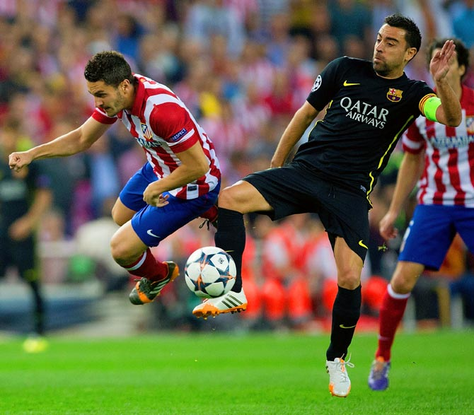 Barcelona's Xavi tackles Koke of Atletico Madrid