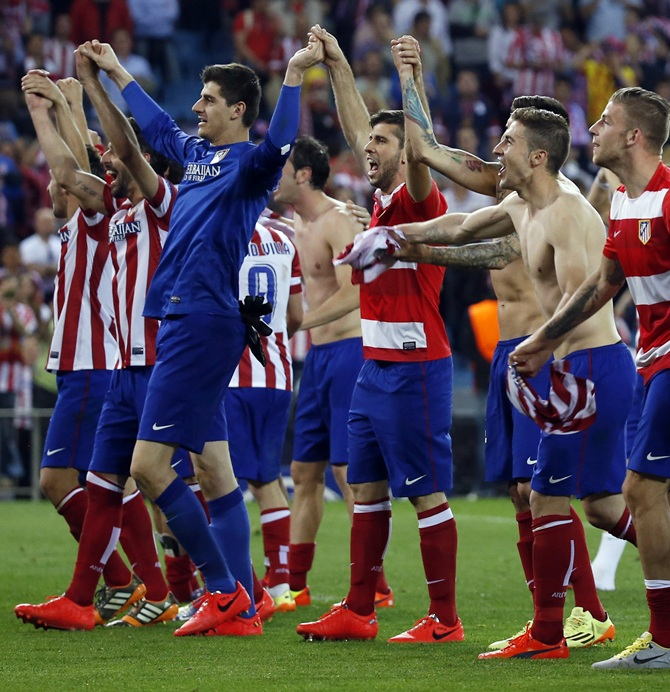 Atletico Madrid players react after winning their Champions League quarter-final second leg soccer match against Barcelona, in Madrid