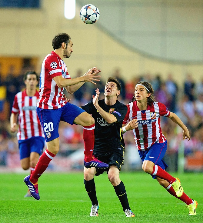 Juanfran of Club Atletico de Madrid climbs above Lionel Messi of Barcelona