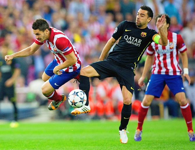 Xavi of Barcelona tackles Koke of Club Atletico de Madrid