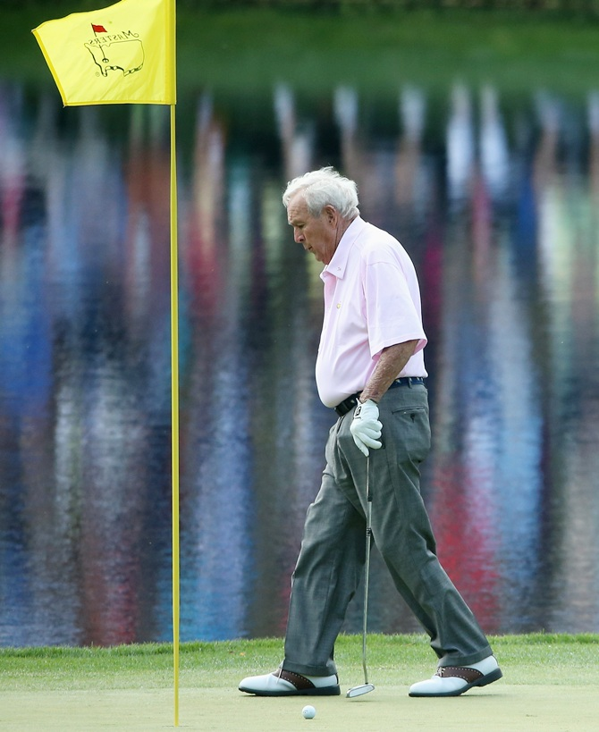 Arnold Palmer walks off a green during the 2014 Par 3 Contest prior to the start of the 2014 Masters Tournament