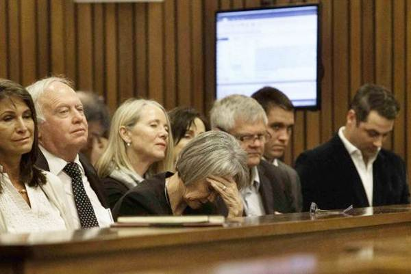 A member of the entourage of Oscar Pistorius holds her head while he testifies during his trial at the North Gauteng high court in Pretoria, on April 10