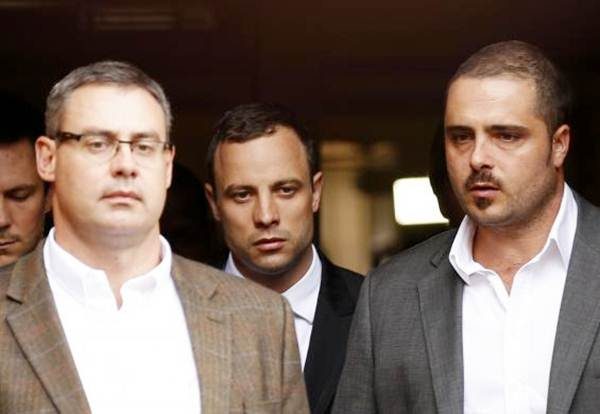 Oscar Pistorius (centre) leaves after his trial at the North Gauteng high court in Pretoria on April 9