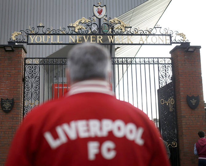 A Liverpool supporter stands in front of the Shankly gates outside Anfield in Liverpool