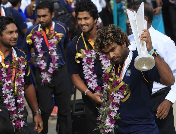 Sri Lanka's Twenty20 cricket team captain Lasith Malinga (right) displays the 2014 WT20 trophy to fans