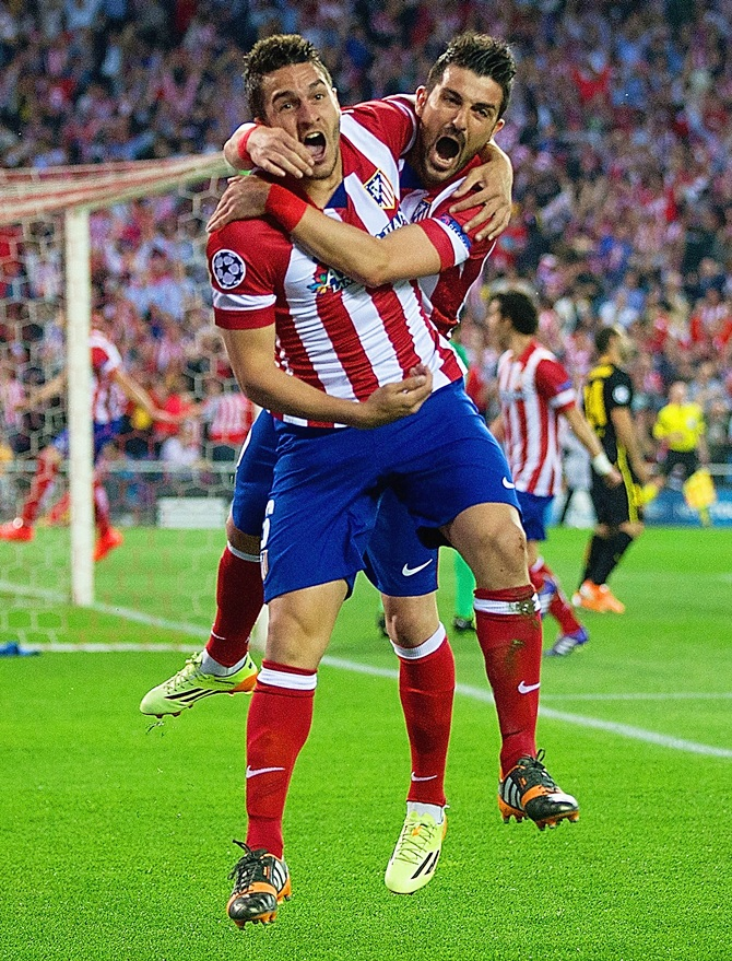 Koke celebrates with Atletico de Madrid teammate David Villa after scoring against Barcelona on Wednesday night in the Champions League