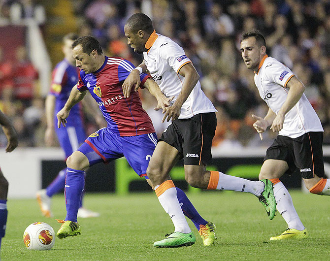 FC Basel's Marcelo Diaz (left) and Valencia's Seydou Keita (centre) vie for possession as Valencia's Paco Alcacer watches on Thursday