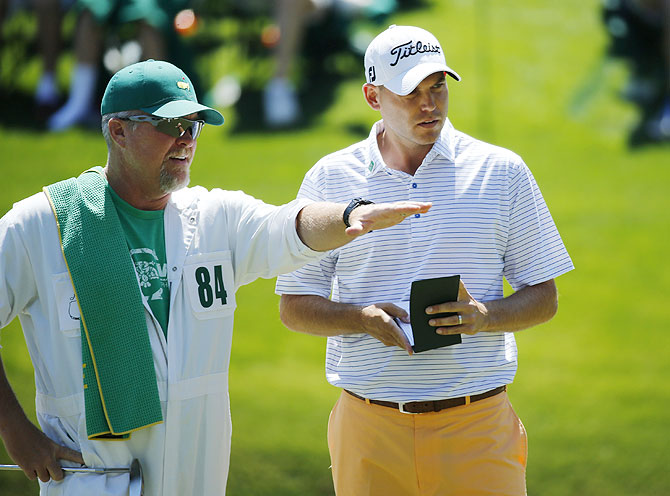 U.S. golfer Bill Haas (right) and his caddie Scott Gneiser discuss a putt on the 16th hole during the first round of the Masters golf tournament at the Augusta National Golf Club on Thursday