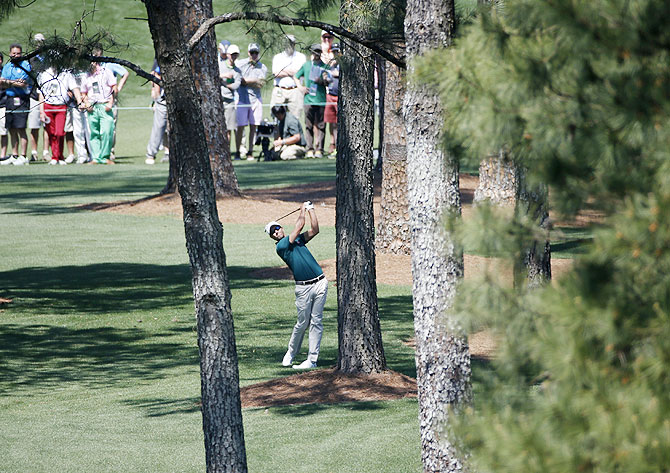Australia's Adam Scott hits a shot from the trees on the seventh hole during the first round of the Masters golf tournament at the Augusta National Golf Club on Thursday