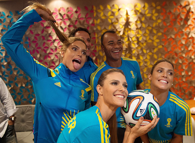 Brazilian former world champions players Juliano Belleti (blurred in background) and former Brazil football captain Cafu (behind right), synchronized swimming athletes Bia (left) and Branca Feres (right) and Brazilian TV presenter and model Fernanda Lima (2nd from left) pose for photo after Volunteers Uniform launch of the 2014 FIFA World Cup during Fashion Rio Summer 2014/2015 at Marina da Gloria in Rio de Janeiro on Thursday