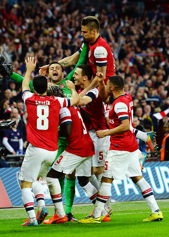 Lukasz Fabianski of Arsenal celebrates winning the penalty shoot out with teammates during the FA Cup Semi-Final against Wigan Athletic at Wembley Stadium in London on Saturday