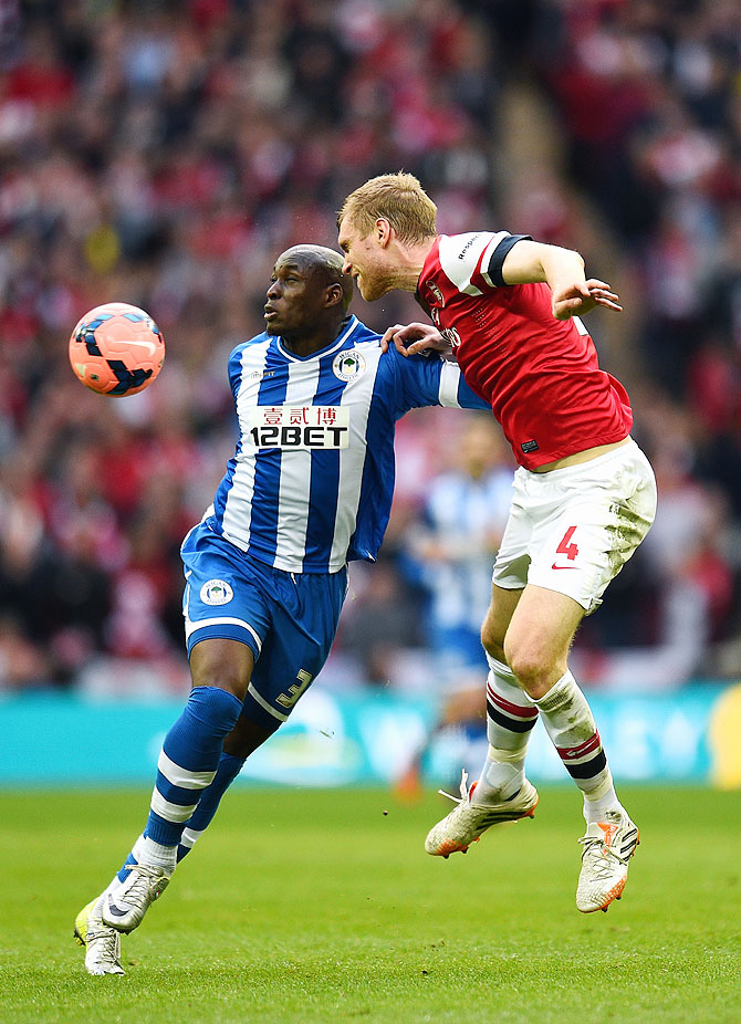 Marc-Antoine Fortune of Wigan Athletic and Per Mertesacker of Arsenal battle for the ball on Saturday