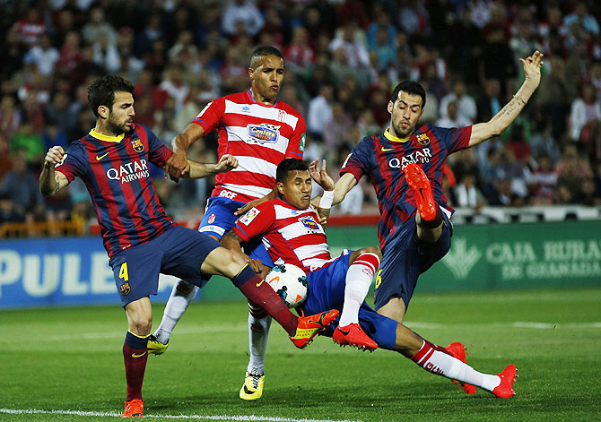 Barcelona's Cesc Fabregas (left) and Sergio Busquets (right) battle for the ball with Granada's Youssef El-Arabi (2nd from left) and Cristian Bravo during their La Liga match on Saturday